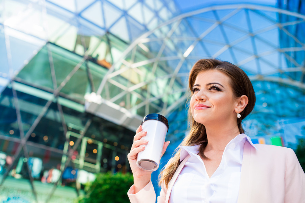 Close up of smiling elegant businesswoman holding thermo coffee cup in pink jacket and white shirt against glassy modern office building