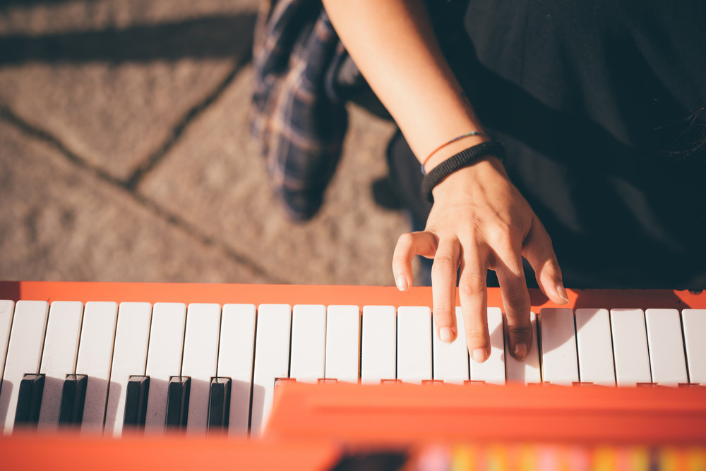 Close up of the hand of young woman playing piano - creative, performance, music concept - she is dressed with a black shirt and plays a red piano