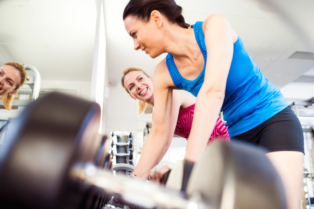 Close up of two attractive fit women in gym working out with weights