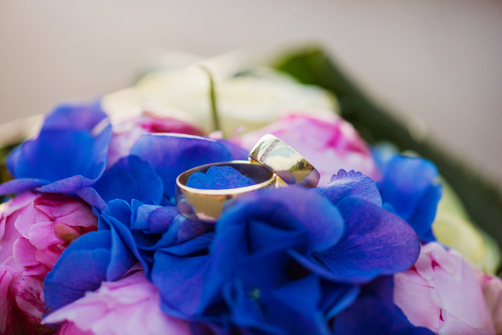 Close up of two wedding rings laid on flower bouquet