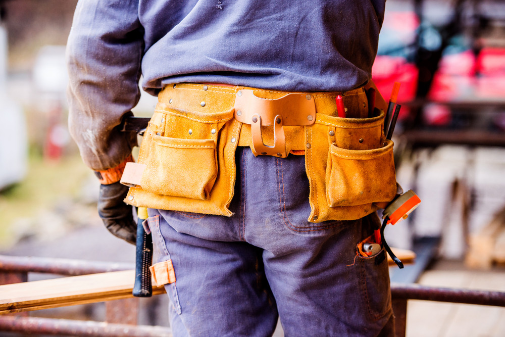 Close up of unrecognizable construction worker with tool bag on site, rear view