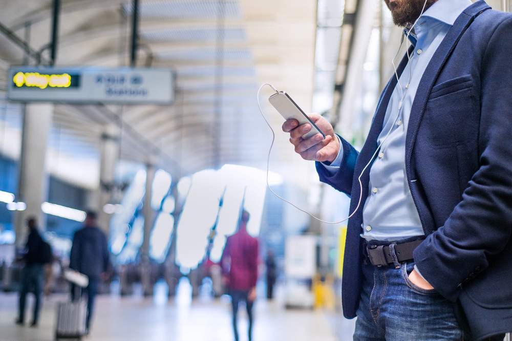 Close up of unrecognizable hipster businessman with smartphone standing on subway station listening music