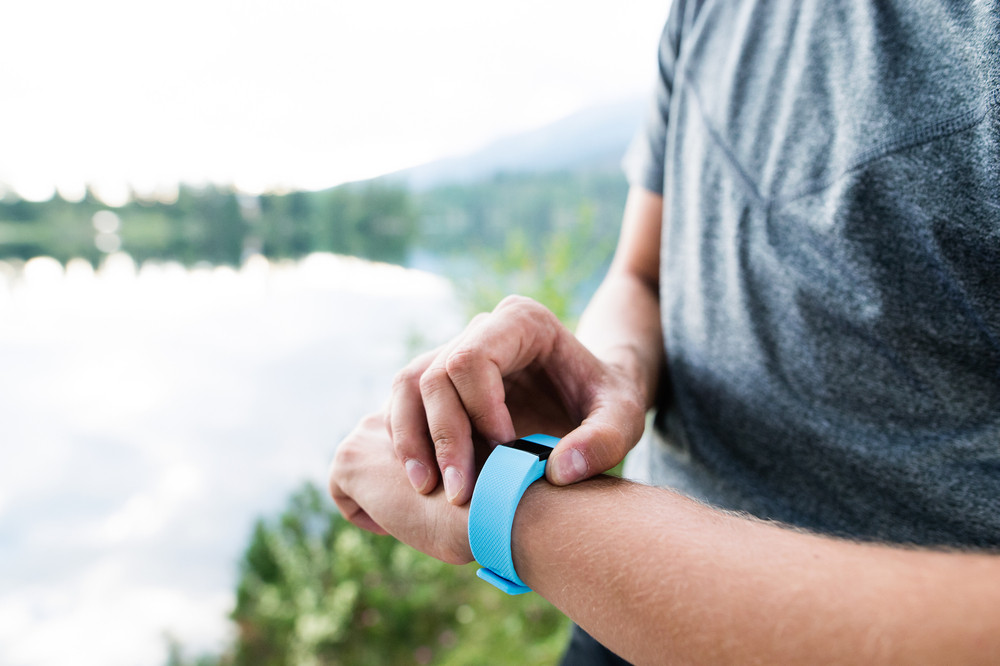 Close up of unrecognizable runner at the lake in green nature wearing smartwatch. Using a fitness app for tracking weight loss progress, running goal or summary of his run.