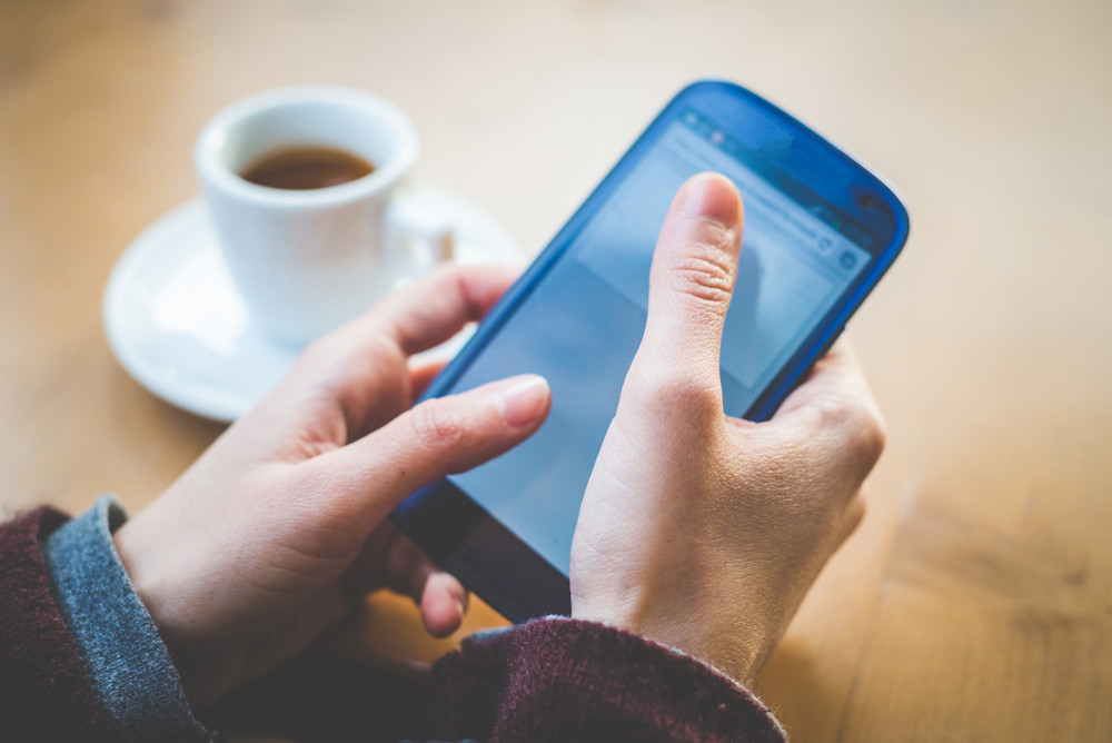 close up of woman hands with smartphone and cup of coffee at the bar