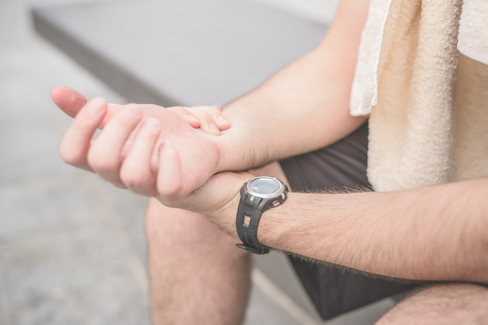 Close up on a sportive young handsome brown hair man checking his heart beats with his wristwatch, looking downward, with a towel around his neck - sportive, healthy, fitness concept
