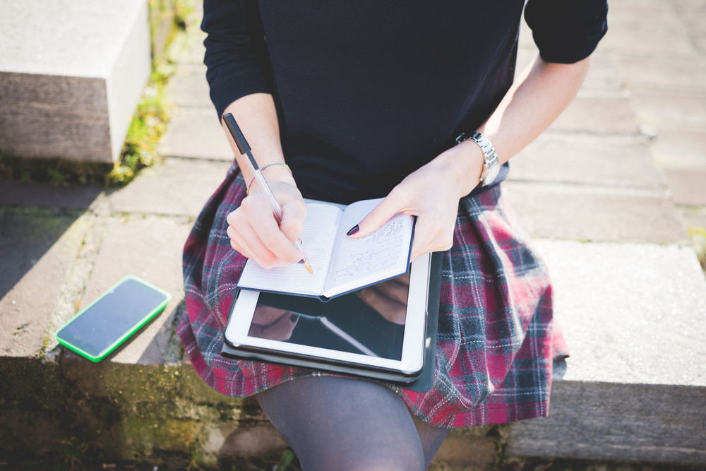 close up on woman hands using tablet, smartphone, and writing on notebook with a pen leaning on her knees - technology, multitasking, working concept