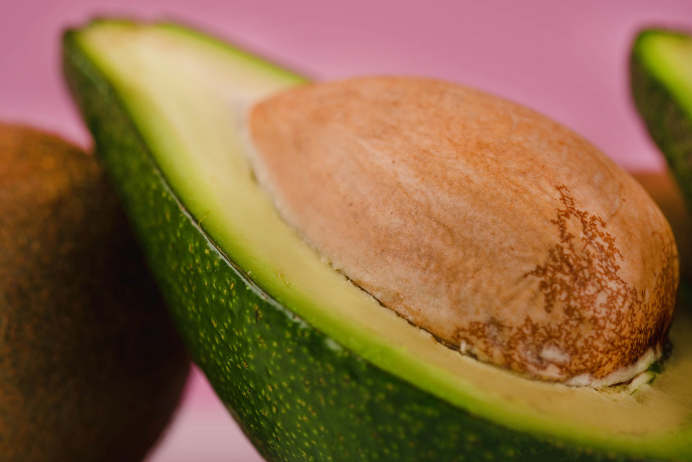 Close up picture of sliced ffresh avocado isolated on pink background