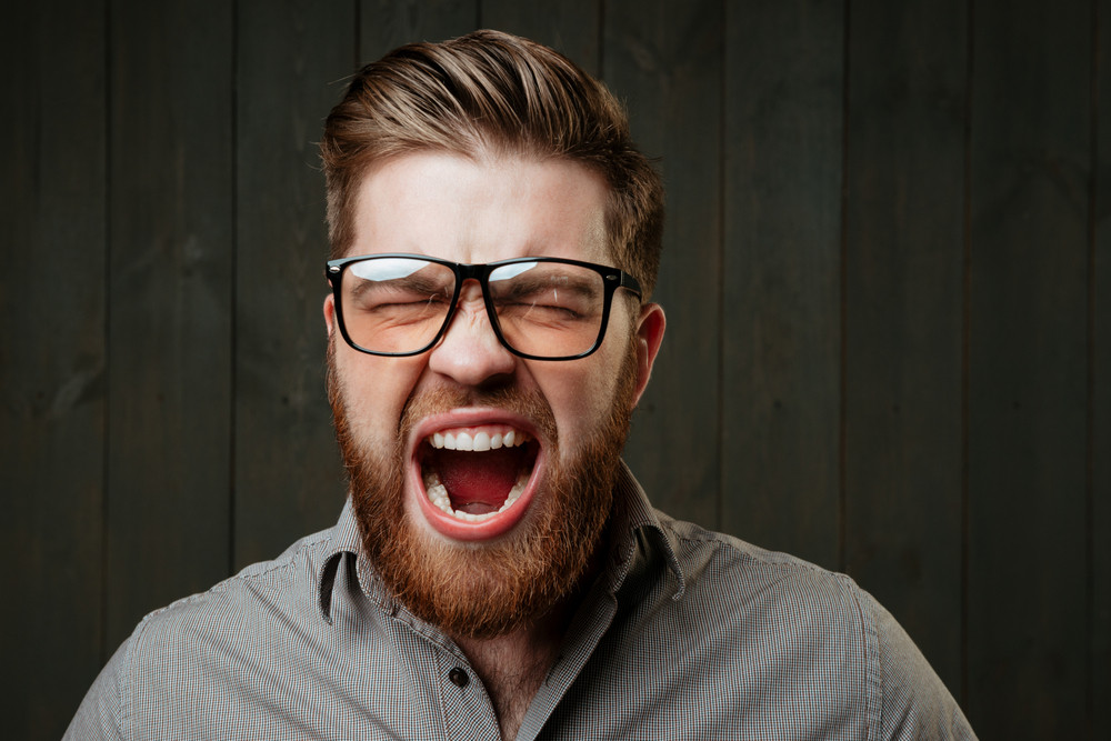 94b65e53a475 Close up portrait of a bearded casual man in eyeglasses screaming with eyes  closed isolated on