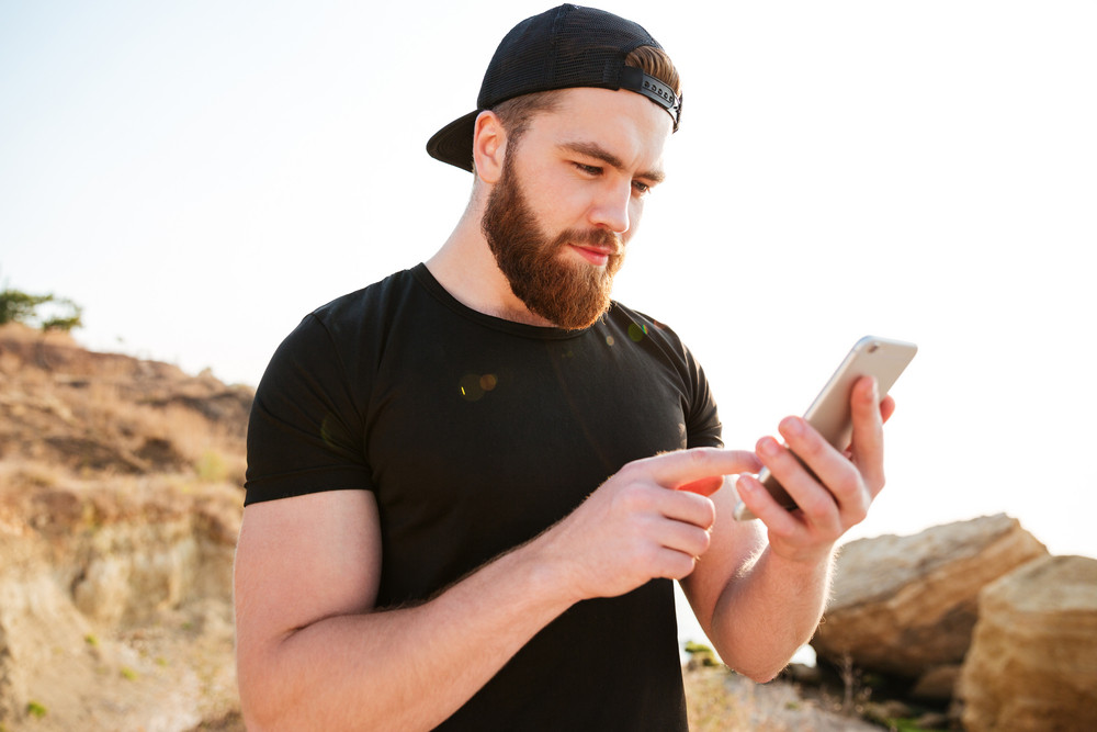 Close up portrait of a bearded young sports man in black t-shirt with smartphone at the beach