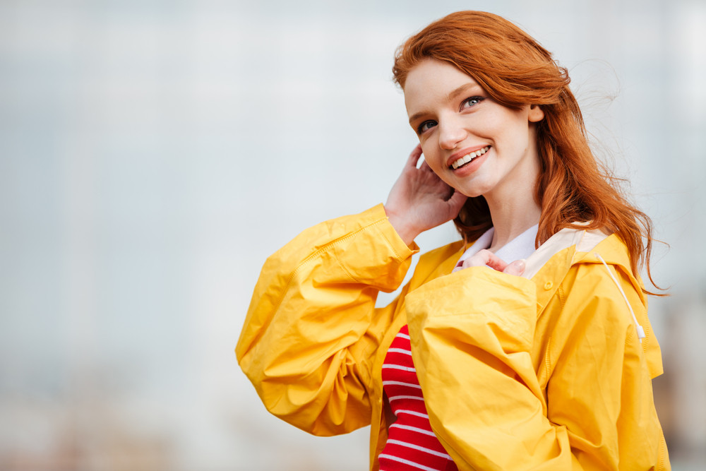 Close up portrait of a beautiful smiling girl with long red hair wearing coat outdoors