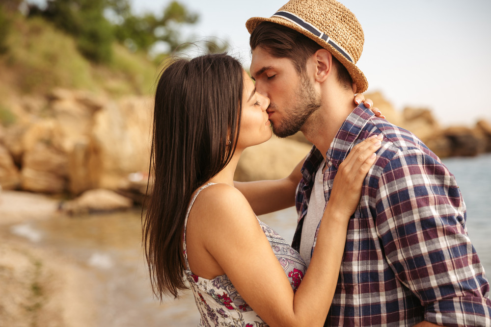 Close up portrait of a beautiful young couple in love standing and kissing on the beach
