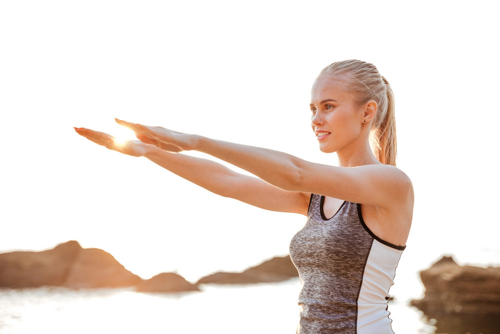 Close up portrait of a beautiful young woman stretching hands exercises during yoga on the beach