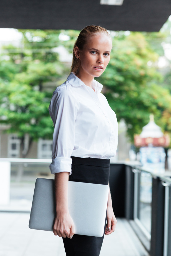 Close up portrait of a blonde businesswoman holding laptop while standing at the balcony outdoors