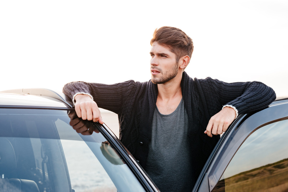 Close up portrait of a casual young man standing near his car outside