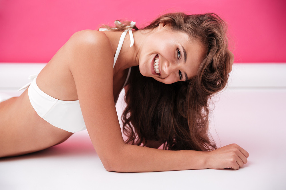 Close up portrait of a cheerful happy girl in white swimsuit lying and looking at camera isolated on the pink background