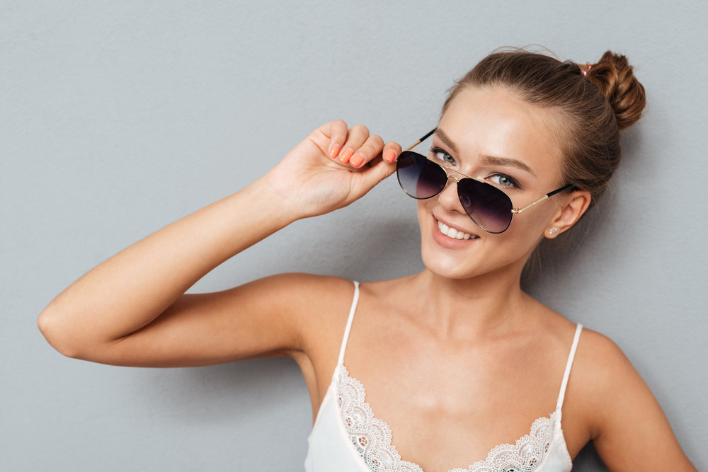 Close up portrait of a cheerful pretty young woman holding sunglasses and looking at camera isolated on a gray background