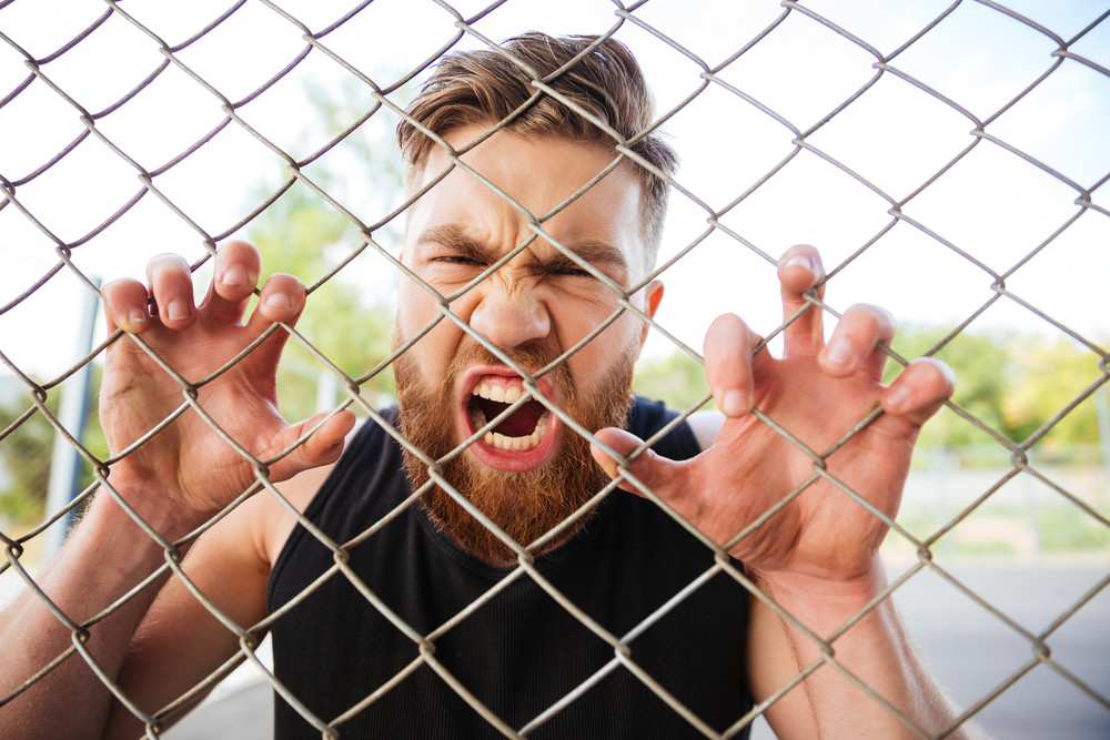 Close up portrait of a crazy bearded man shouting with his hands on metal fence outdoors