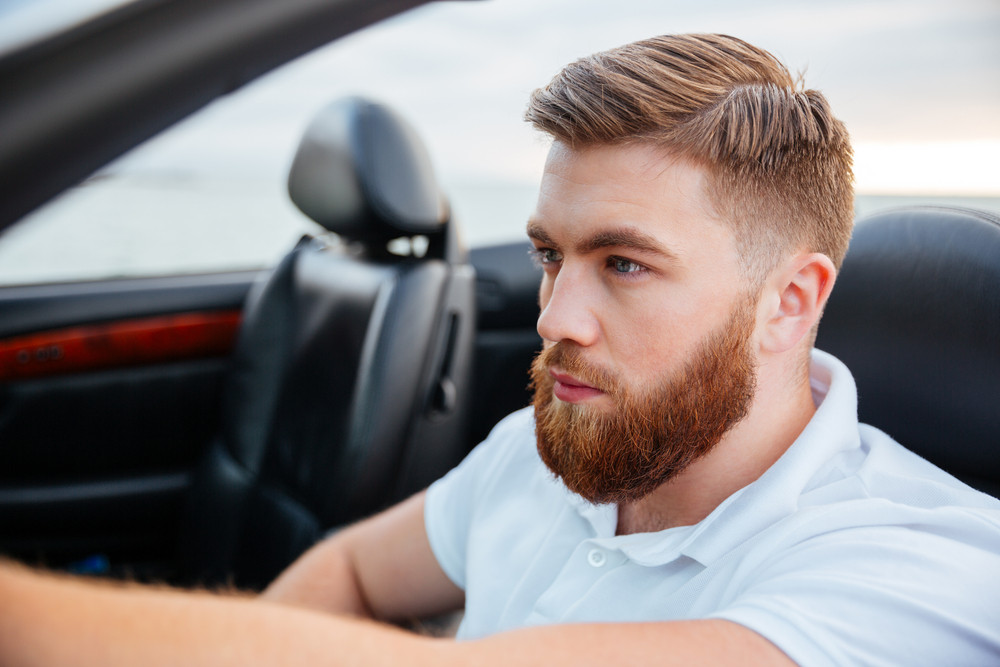 Close up portrait of a handsome bearded man driving luxury car