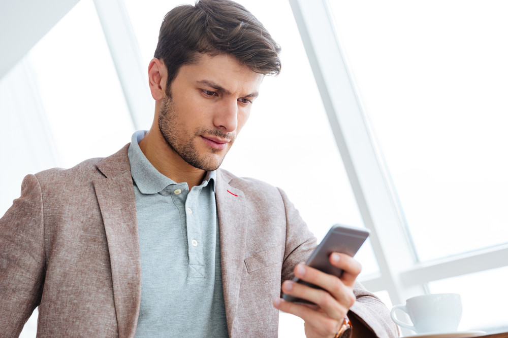 Close up portrait of a handsome casual businessman using smartphone indoors