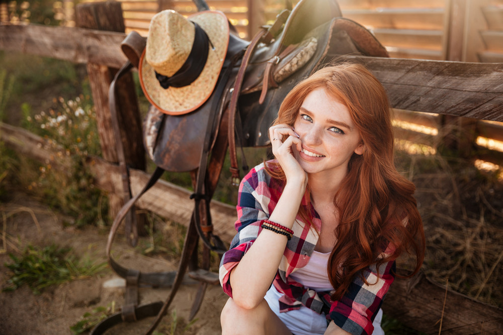 Close up portrait of a happy beautiful redhead cowgirl resting at the ranch fence