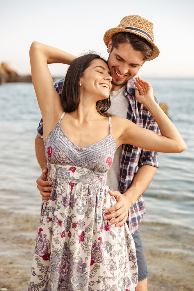 Close up portrait of a happy young couple in love standing at the beach and hugging