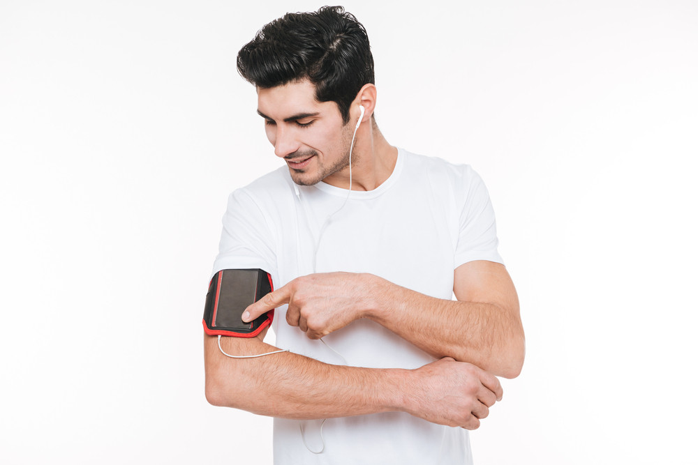 Close up portrait of a happy young sportsman using blank screen mobile phone on armband isolated on a white background