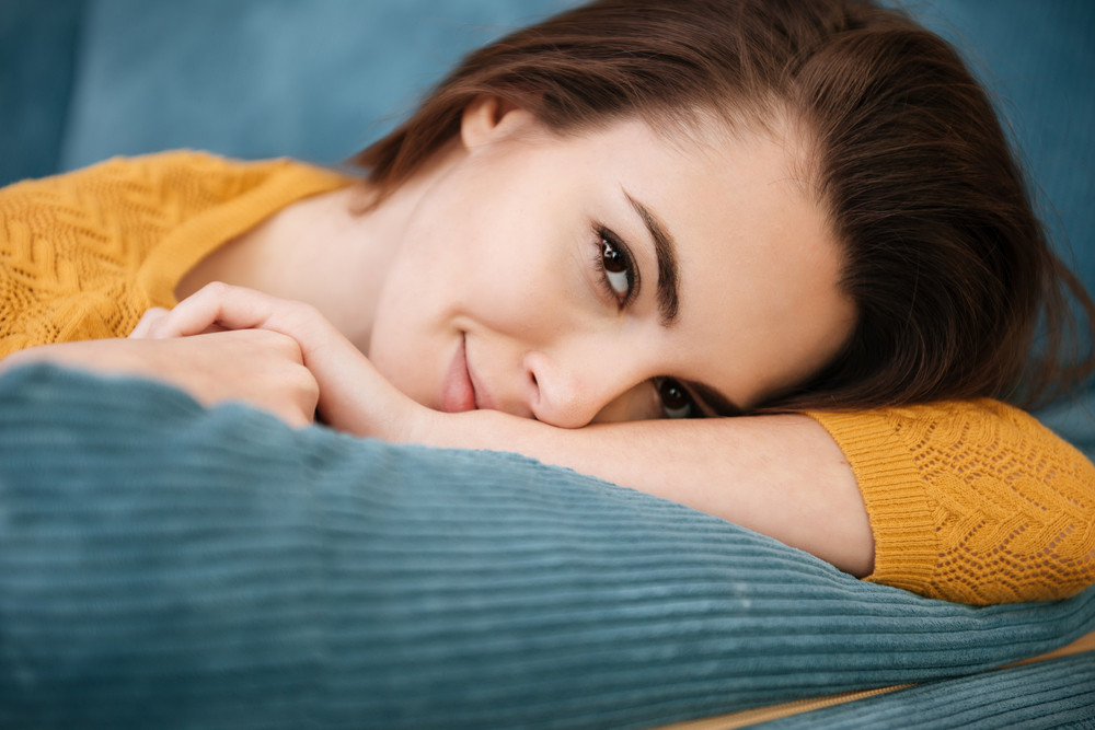 Close up portrait of a lovely young girl lying on a pillow and looking at camera at home
