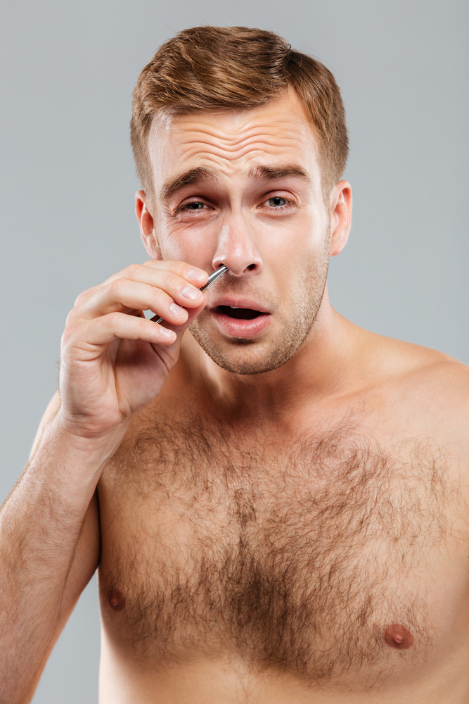 Close-up portrait of a man removing nose hair with tweezers isolated on the gray background