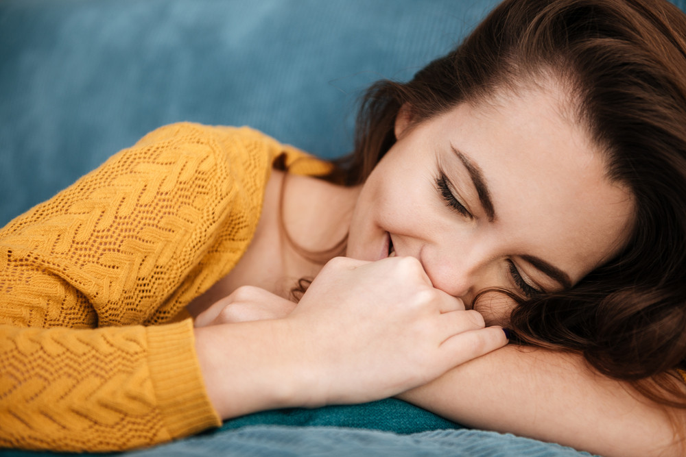 Close up portrait of a pretty lovely woman lying on a couch and laughing indoors