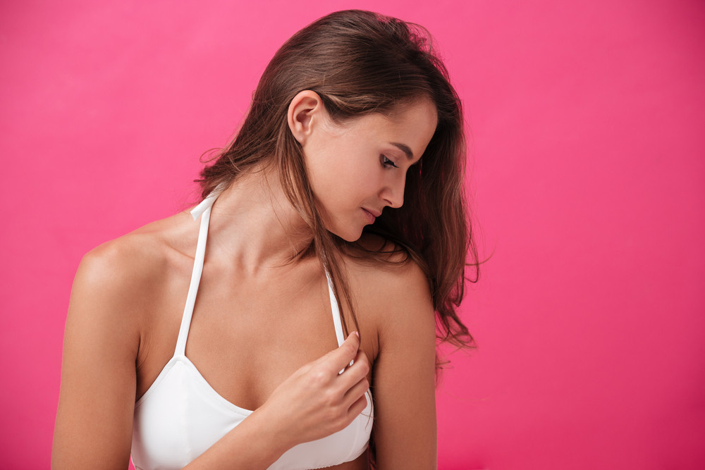 Close up portrait of a pretty young girl in white bikini over pink background