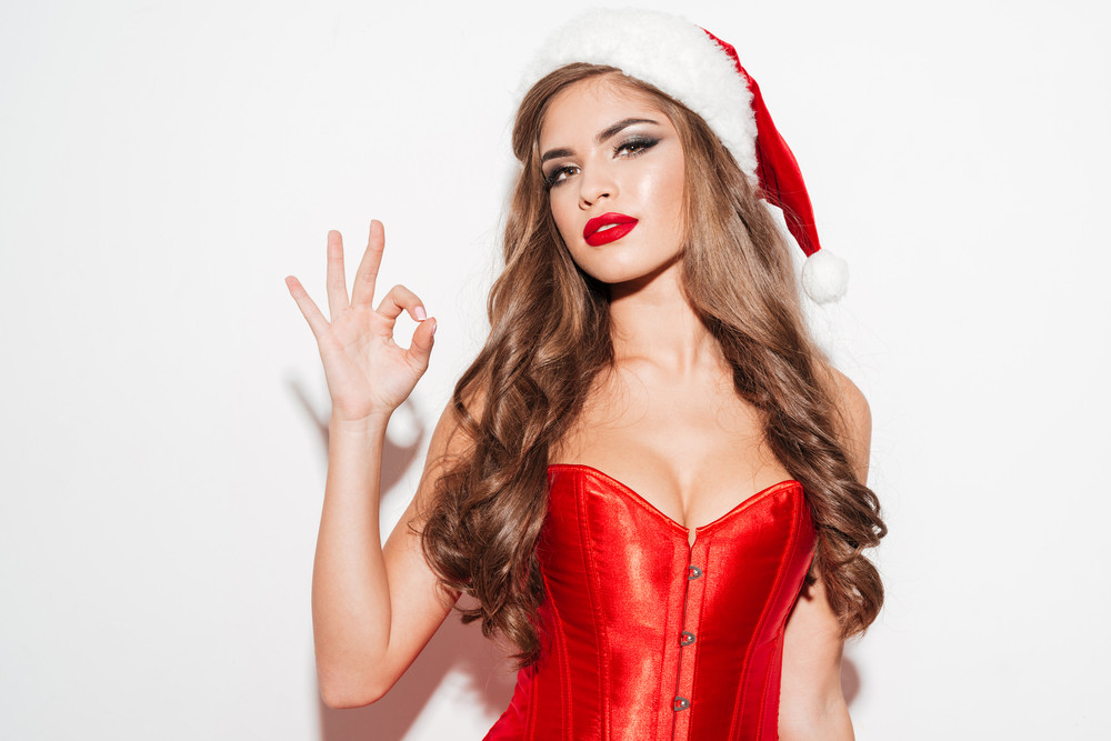 Close up portrait of a seductive beautiful woman in red dress and hat showing okay gesture isolated on the white background