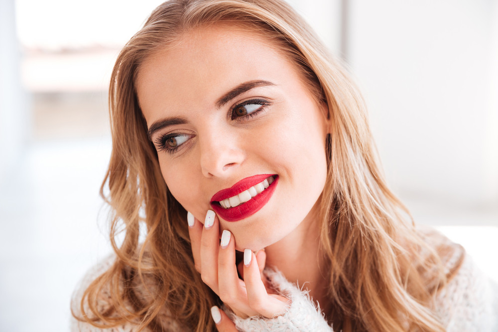 Close up portrait of a smiling attractive woman with red lipstick indoors