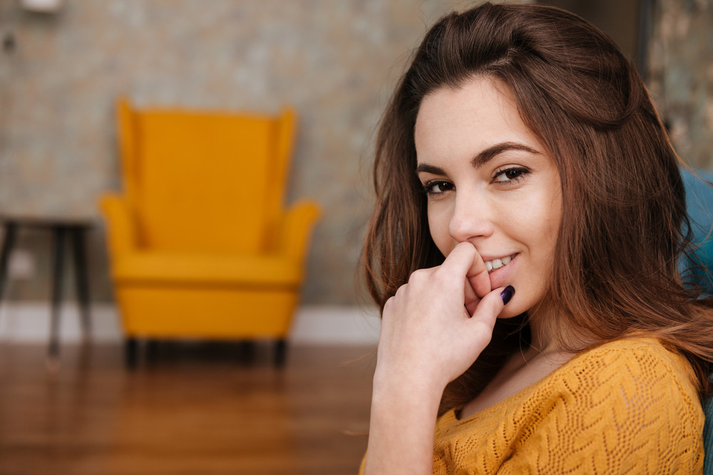 Close up portrait of a smiling charming woman looking at camera in the living room