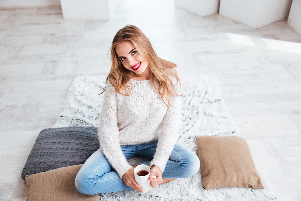 Close up portrait of a smiling happy girl in sweater holding tea cup and looking at camera indoors