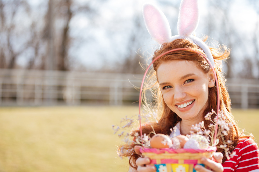 Close up portrait of a smiling happy red head girl wearing bunny ears and holding basket with painted easter eggs outdoors