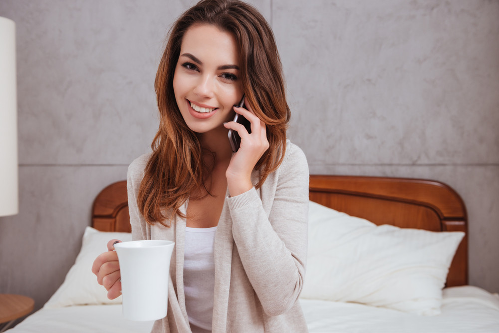 Close up portrait of a smiling happy woman talking on mobile phone and drinking cup of tea while sitting on bed