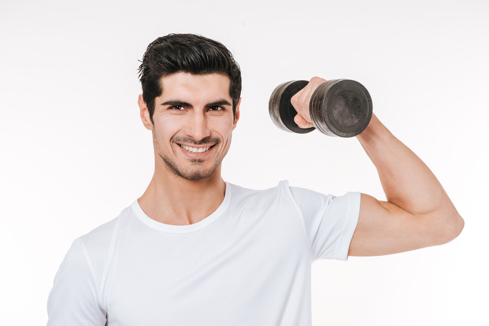 Close up portrait of a smiling young bodybuilder holding heavy dumbbell isolated on a white background