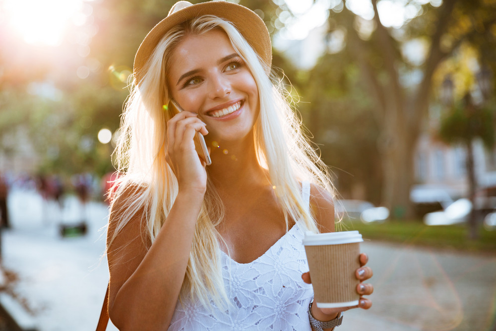 Close up portrait of a smiling young girl in hat holding take away coffee cup and talking on smartphone on the street