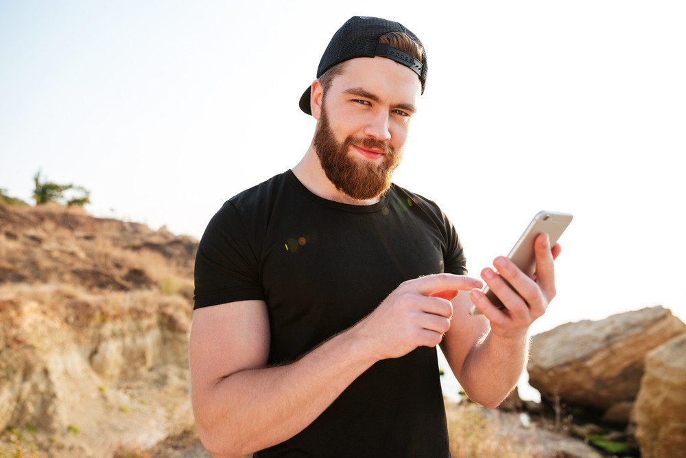 Close up portrait of a smiling young sports man using smartphone and looking at camera