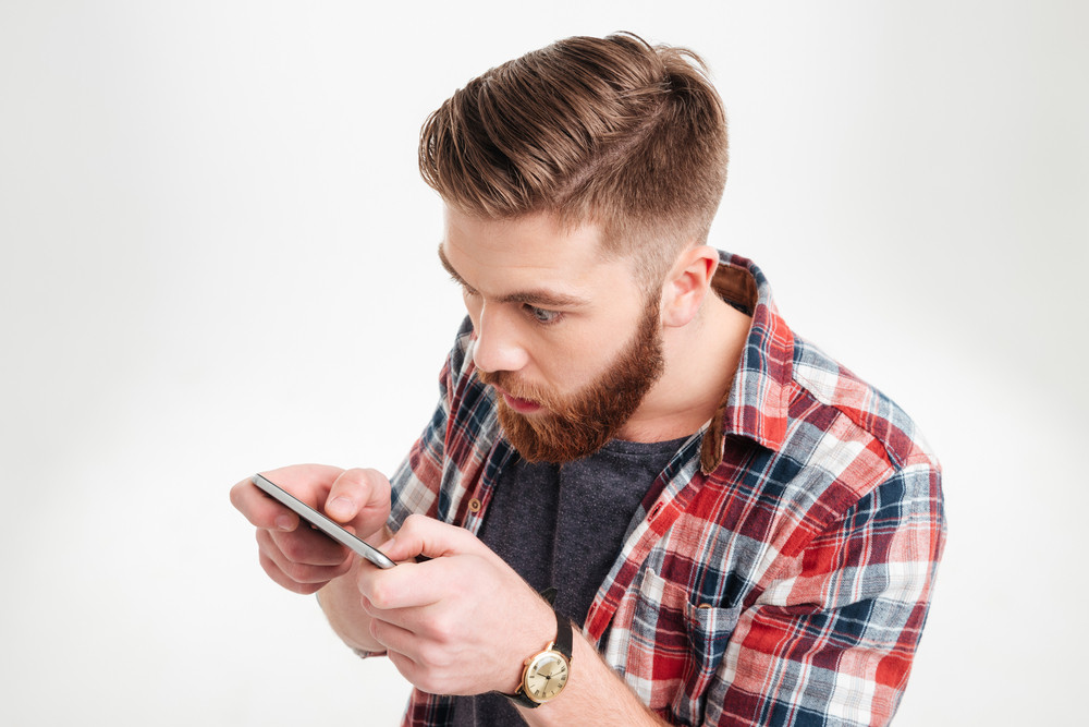 Close up portrait of a surprised casual man looking at mobile phone over white background