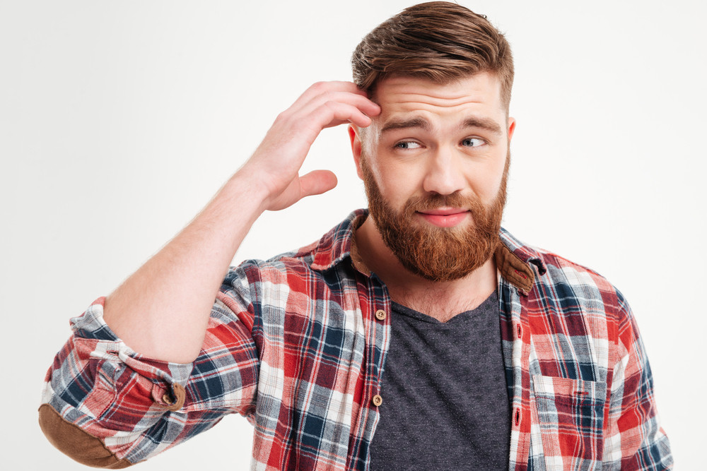 Close up portrait of a thoughtful bearded man in checkered shirt touching his face isolated on a white background
