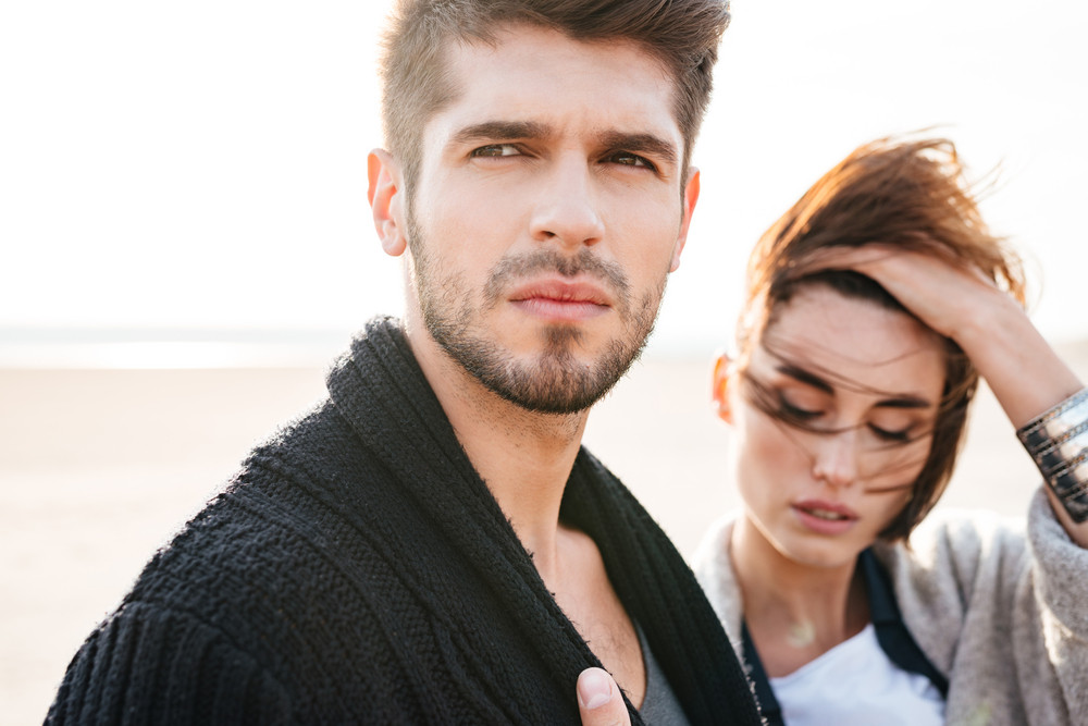 Close up portrait of a young attractive couple at the beach