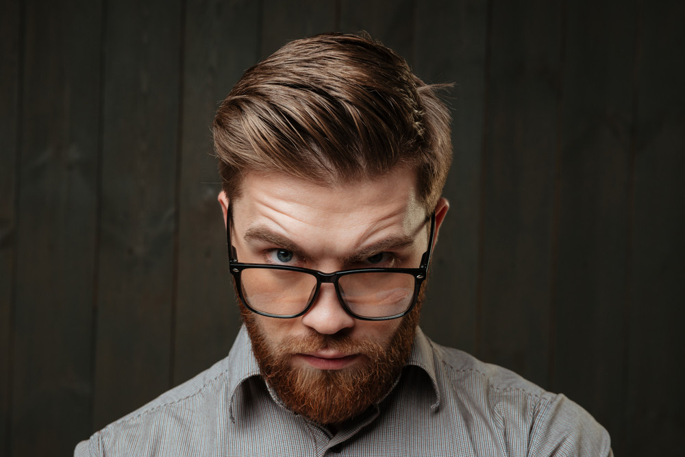 Close up portrait of a young bearded man staring at camera over his glasses isolated on the black wooden background
