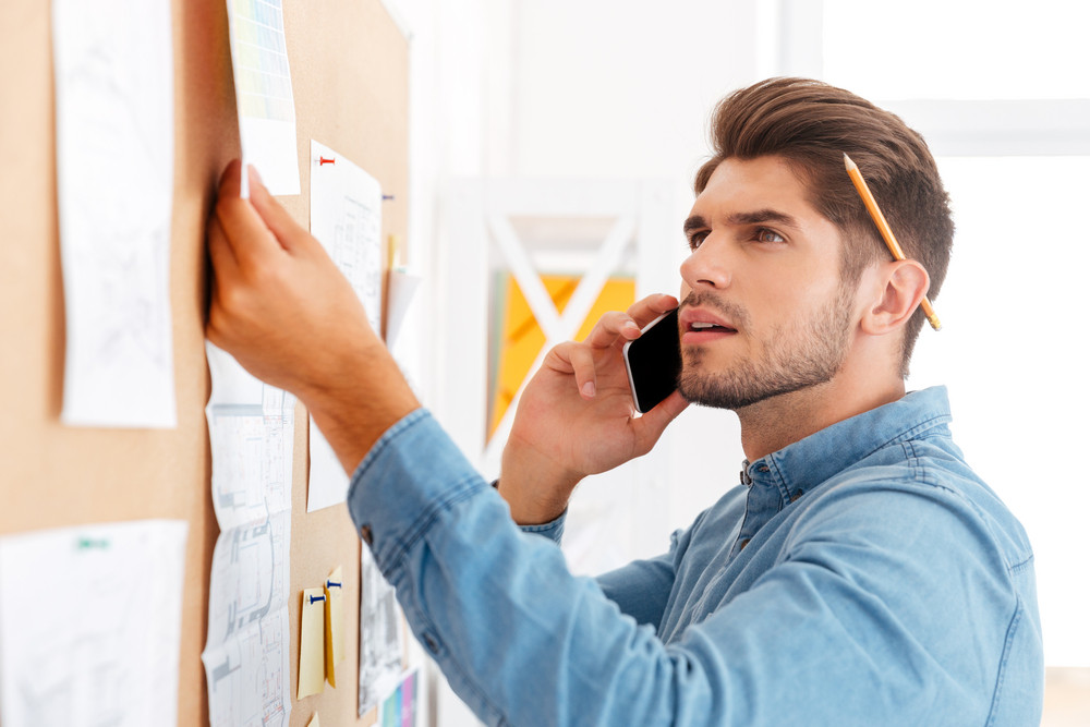 Close up portrait of a young casual concentrated businessman looking at office task board and talking on the phone