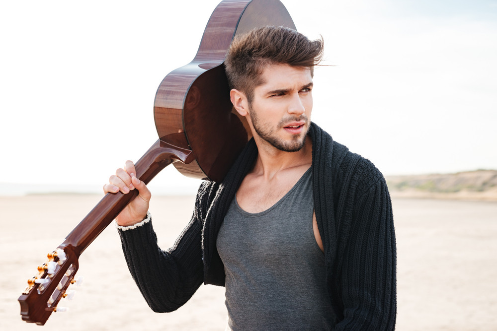 Close up portrait of a young casual man with guitar on his shoulder on the beach