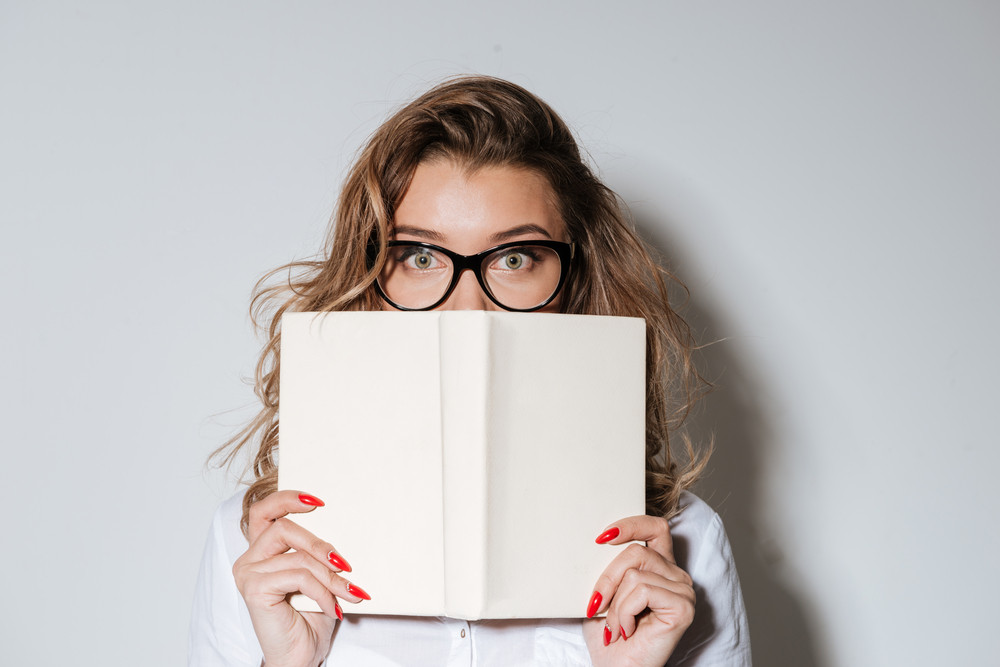 Close up portrait of a young woman in eyeglasses covering her face with book isolated on the white background