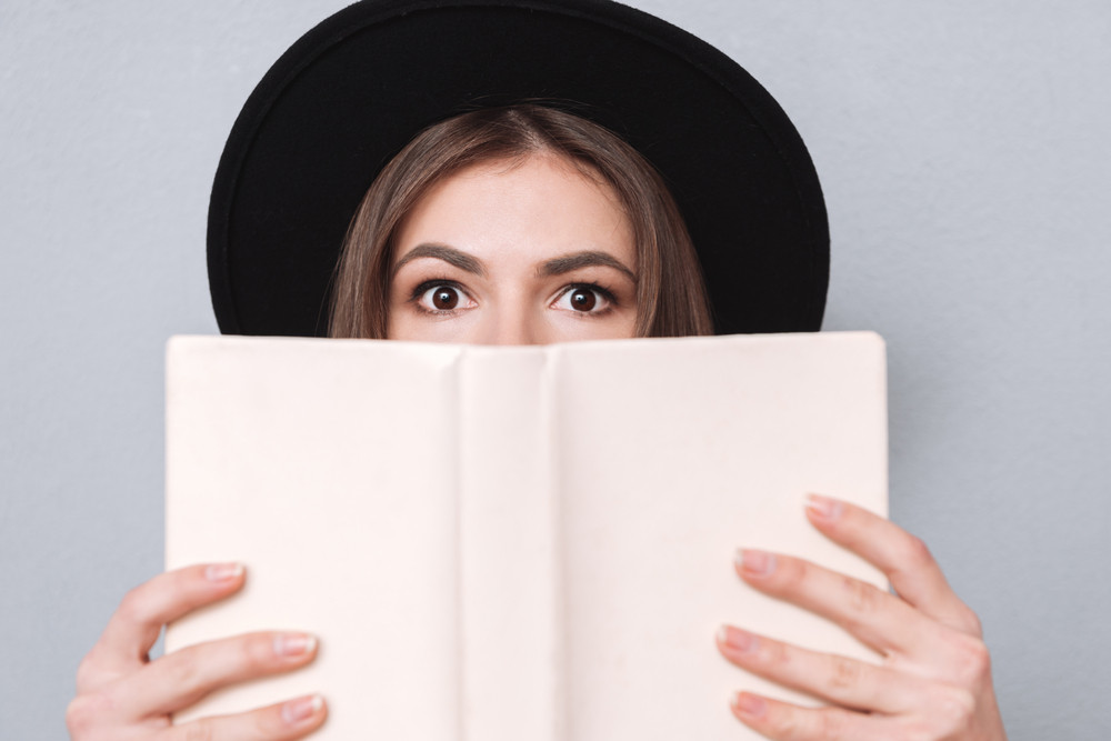 Close up portrait of a young woman in hat covering her mouth with book isolated on the gray background