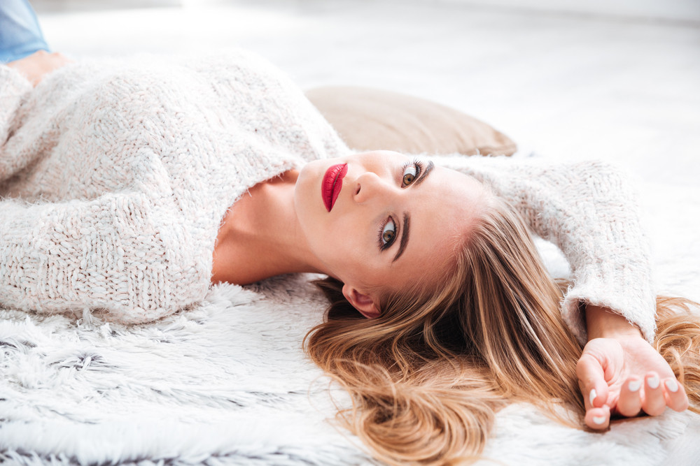Close up portrait of an attractive young woman in sweater lying on the carpet at home