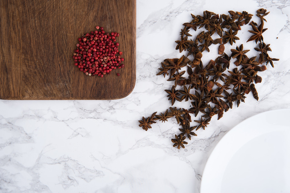 Close up portrait of anise seeds and spicy red pepper on wooden cutting board on white marble background