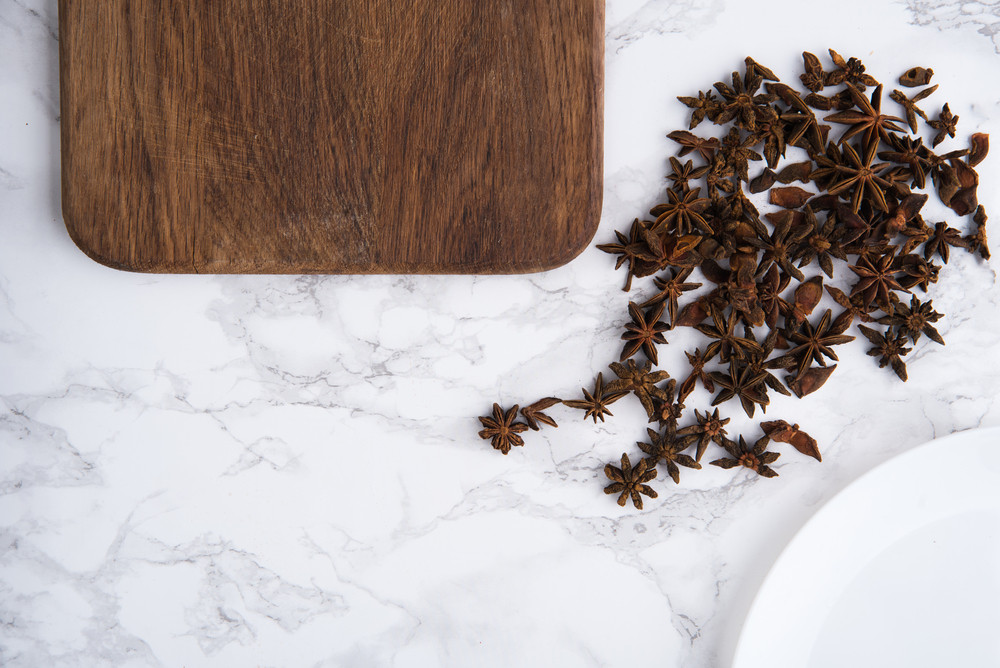Close up portrait of anise seeds and wooden cutting board on white marble background